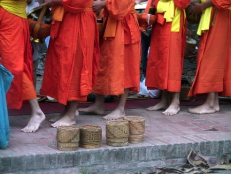 Monk feet do the saffron march past some alms